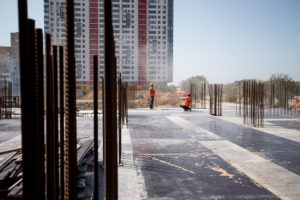 The building site against the background of a multistorey building. Two builders are working